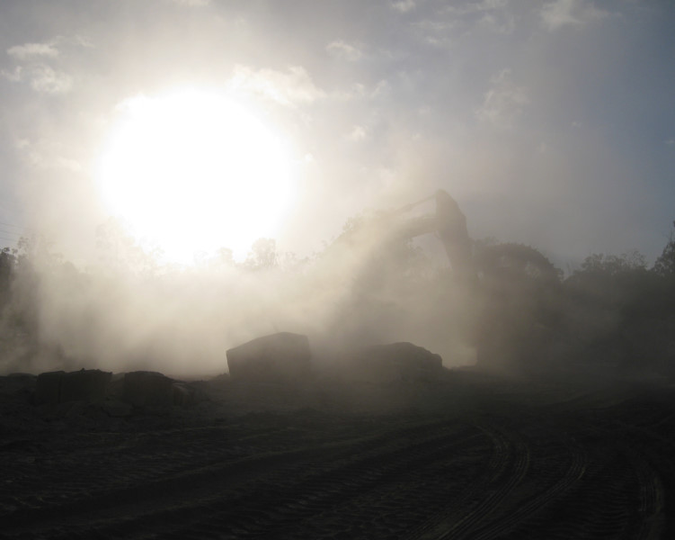 Excavator operating in typical dust plume